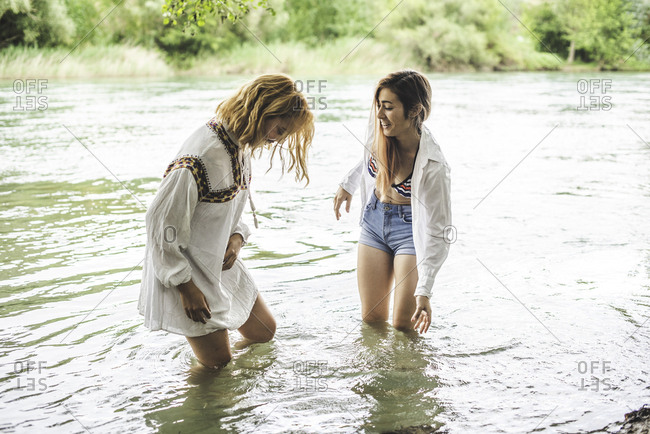 Two young women wading in river together