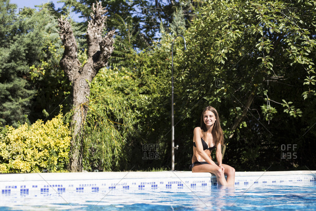 Young woman in bikini sitting poolside looking at camera in Madrid, Spain