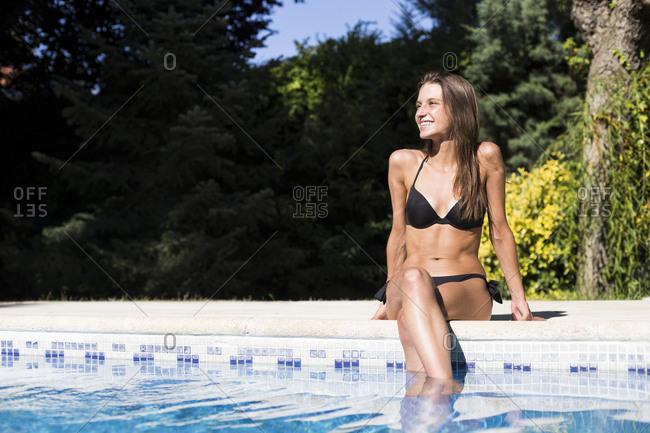 Young woman in bikini smiling sitting poolside looking away in Madrid, Spain