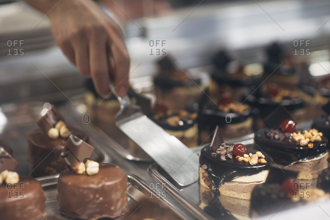 Hand of unrecognizable person taking cake from tray at cake shop.