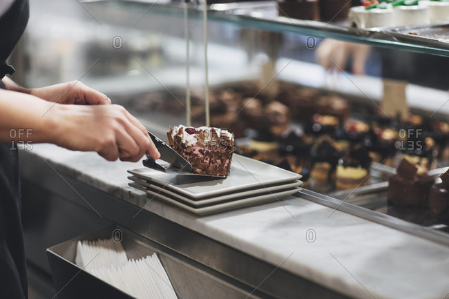 Hands of unrecognizable waitress at coffee shop putting cake on plate.