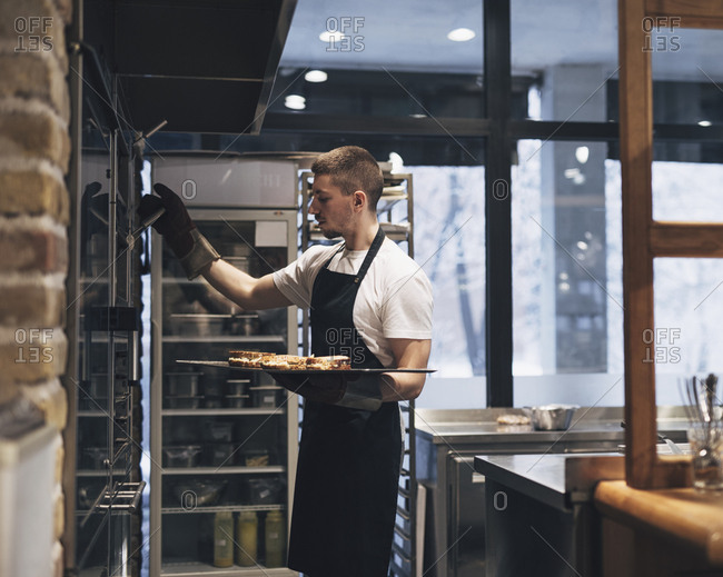 Man cook wearing apron and putting food in kitchen oven.