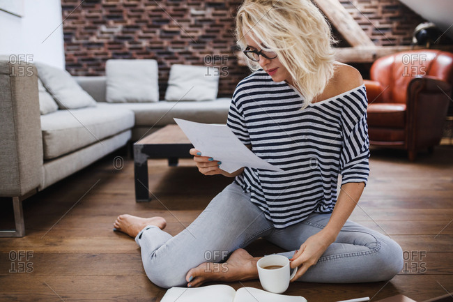 Pretty Caucasian blonde woman freelancer sitting on the floor and reading paper document.
