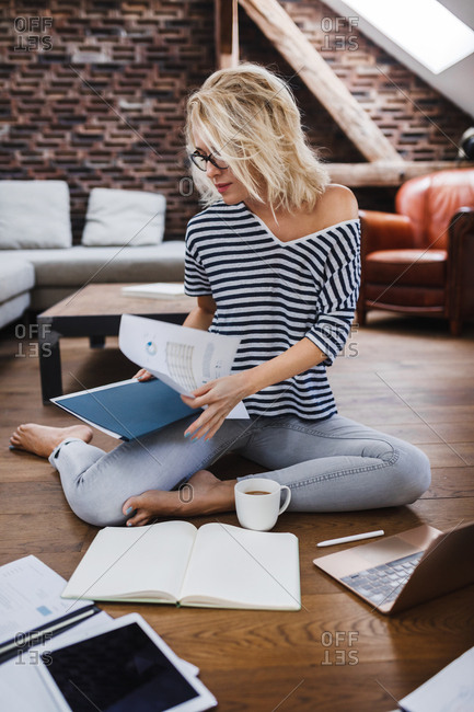 Pretty Caucasian blonde woman freelancer sitting on floor and folding documents.
