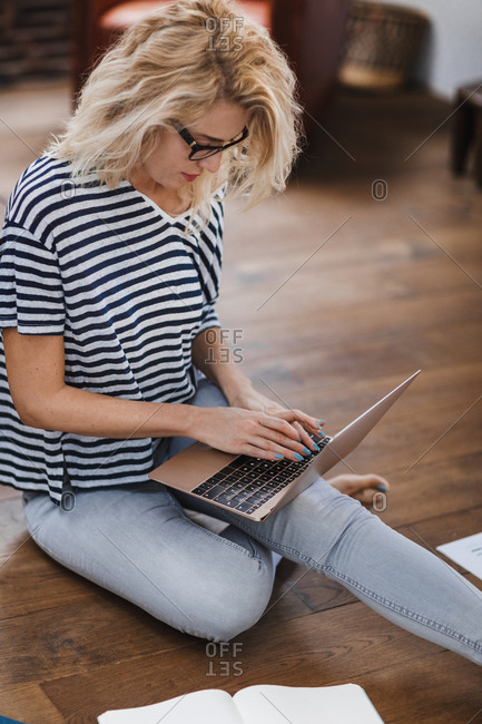 Pretty Caucasian blonde woman freelancer sitting on floor and typing on her laptop.