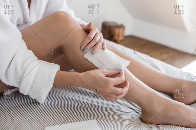 Unrecognizable woman waxing her legs at home.