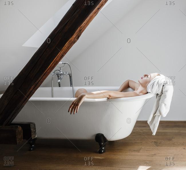 Pretty Caucasian woman relaxing in bathtub.