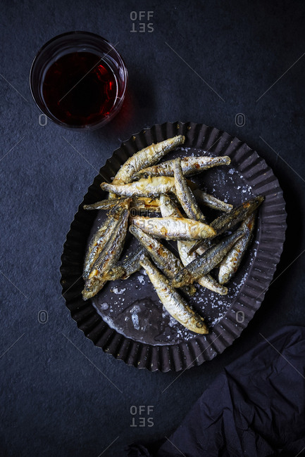 Deep Fried white bait on black countertop with red wine;