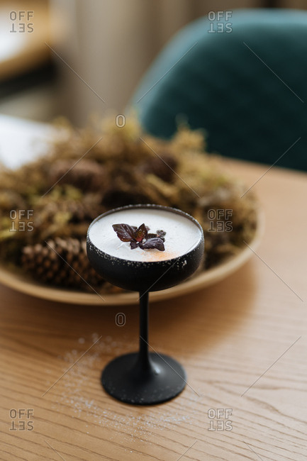 Frothy cocktail in black stemware