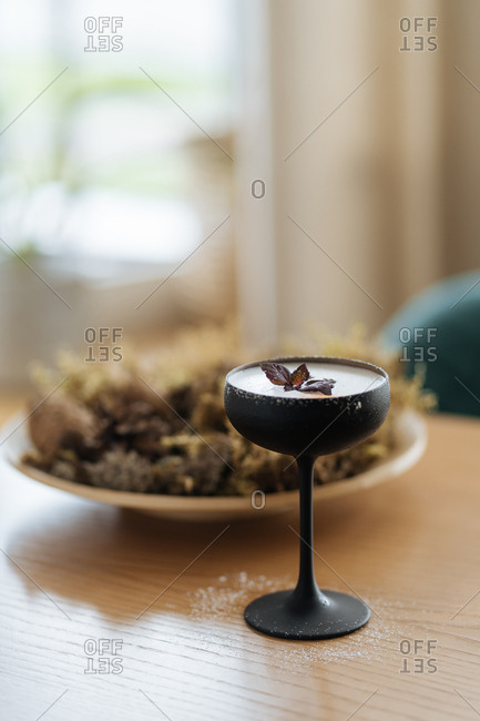 Frothy cocktail in black glass