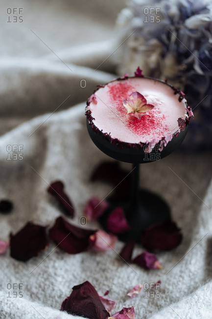 Frothy pink cocktail with flowers in black glass