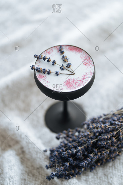 Frothy cocktail with lavender in black glass
