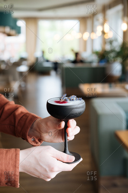 Man holding a frothy cocktail with lavender in black glass in a restaurant