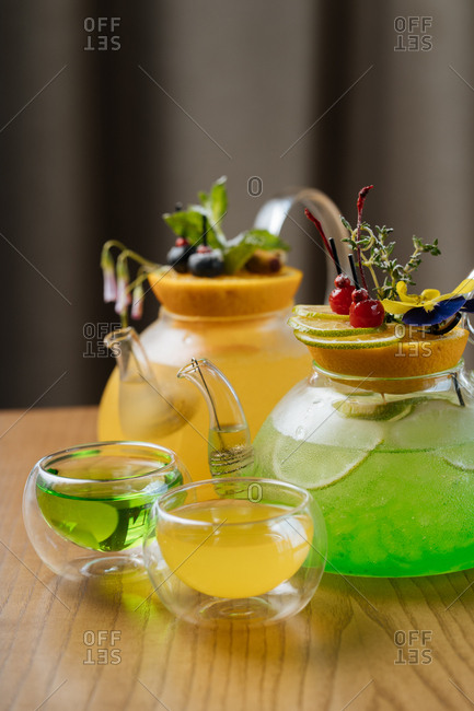 Two colorful cocktails in glass kettles