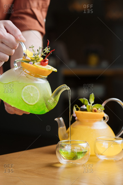 Man pouring colorful cocktails in glass kettles