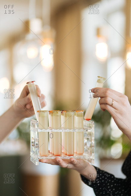 Women grabbing test tube shots
