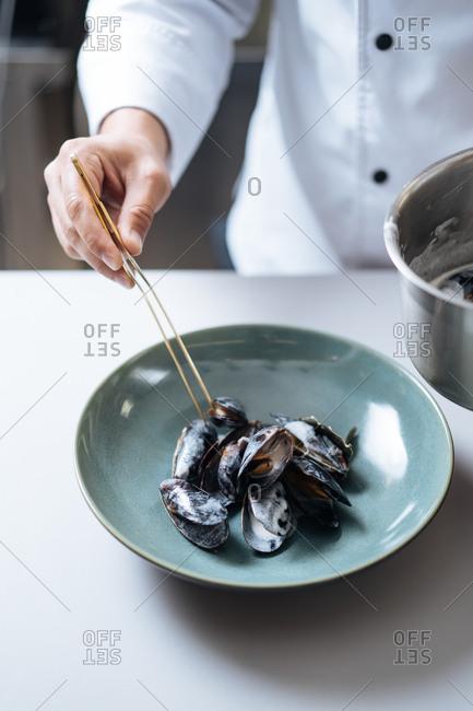 Chef preparing mussel seafood dish