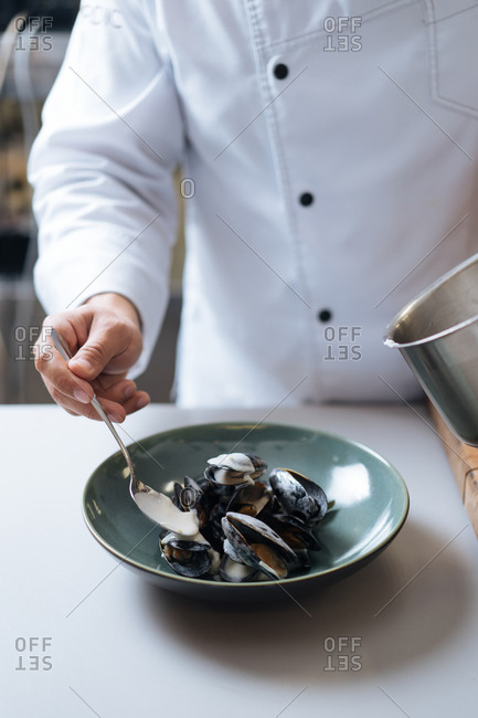 Chef pouring sauce on mussel seafood dish