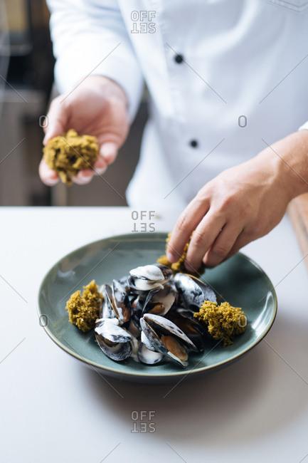 Chef preparing mussel dish in a restaurant