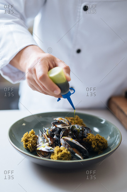 Chef drizzling sauce over mussel dish in a restaurant