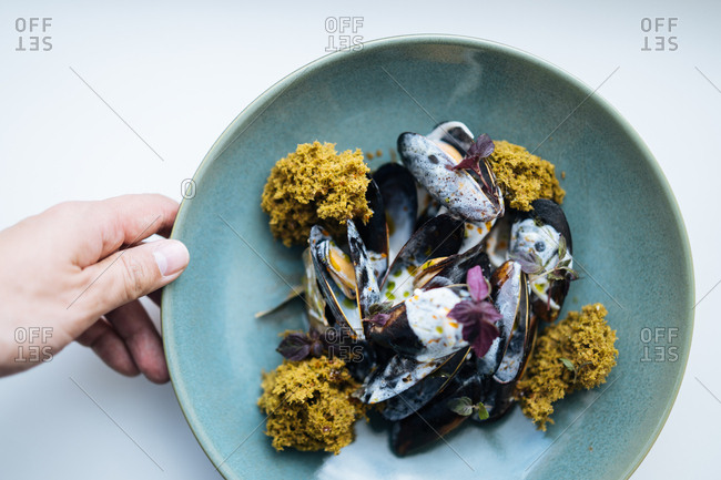 Hand holding freshly prepared mussel dish