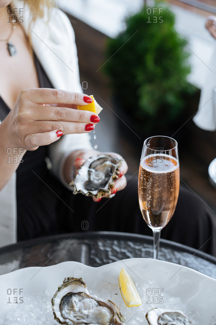 Woman squeezing lemon juice on oysters and drinking champagne