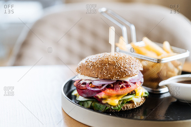 Gourmet cheeseburger and fries served in a restaurant