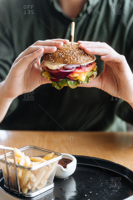 Man eating cheeseburger and fries served in a restaurant