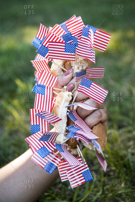 A person squeezing a hot dog in a bun with American flag toothpicks stuck in it