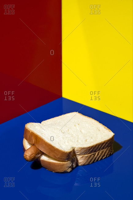 A hot dog is tucked in between two pieces of sliced white bread on primary color backgrounds