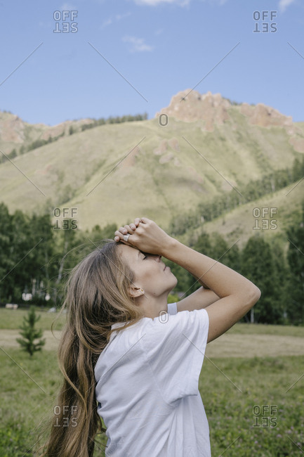 Profile view of blonde woman standing in front of mountain