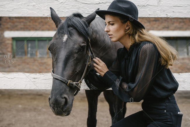 Woman dressed in black with a black horse