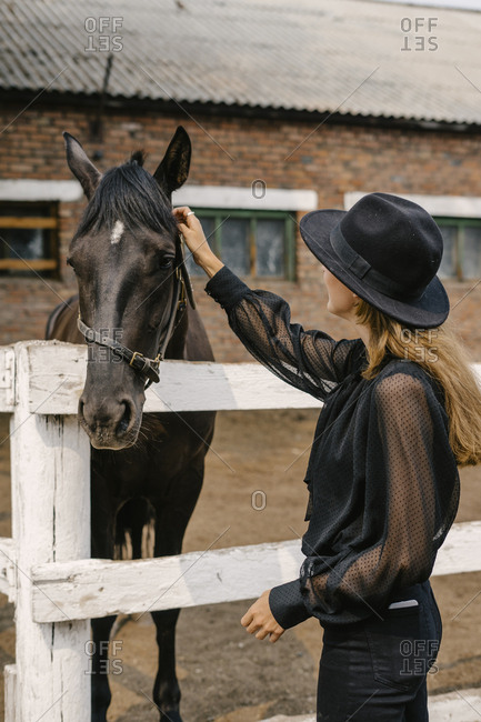 Woman dressed in black petting a black horse