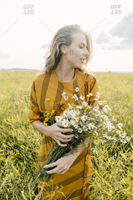 Attractive blonde woman holding wildflower bouquet in a field