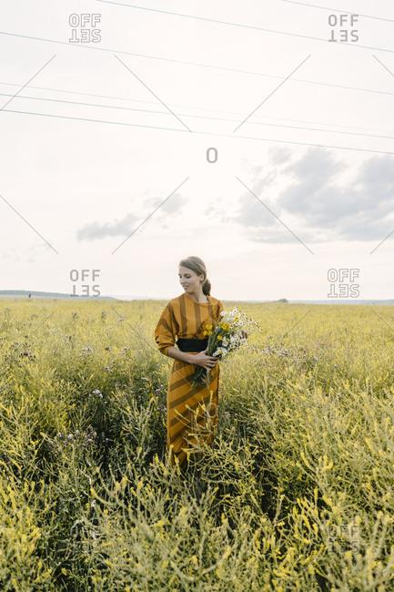 Blonde woman holding wildflower bouquet in a field