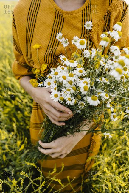 Woman holding wildflower bouquet in a field
