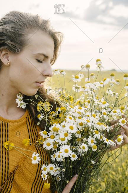 Blonde woman smelling wildflower bouquet in a field