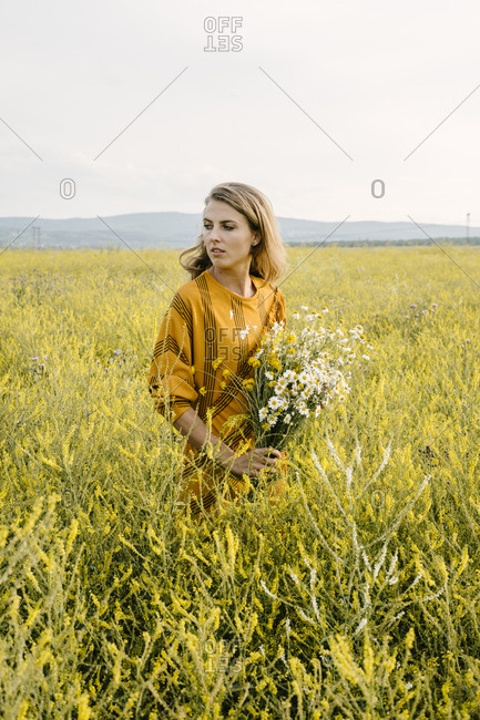 Young woman holding daisy bouquet in a field
