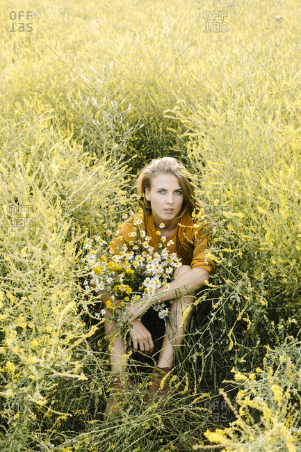 Young woman sitting in a field with wildflowers