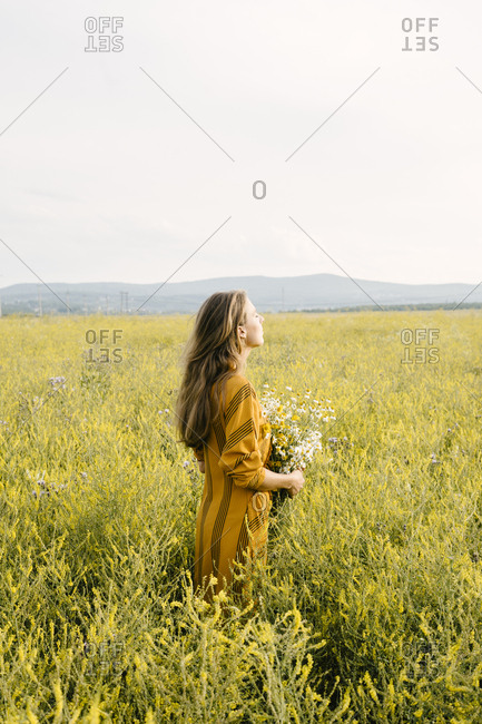 Side view of woman holding daisy bouquet in a field
