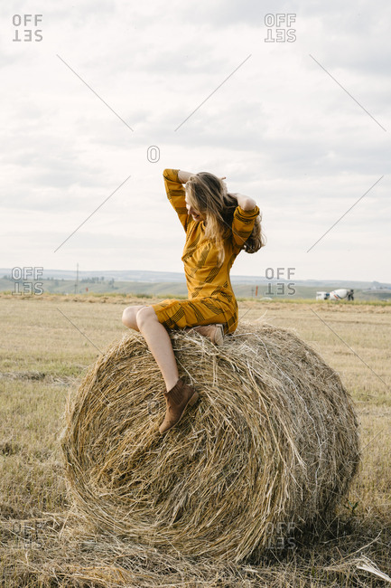 Blonde woman sitting on a bale of hay in a field