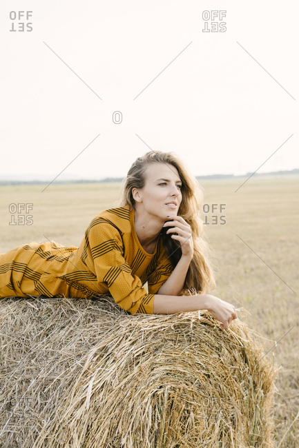 Blonde woman lying on a bale of hay