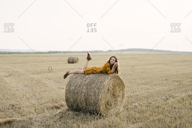 Blonde woman lying on a bale of hay in a field