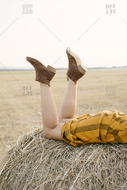 Focus of boots of a woman lying on a bale of hay