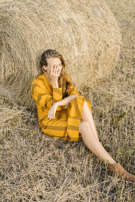 Happy woman sitting beside bale of hay in a field
