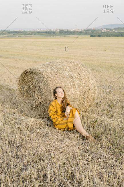 Blonde woman sitting beside bale of hay in a field