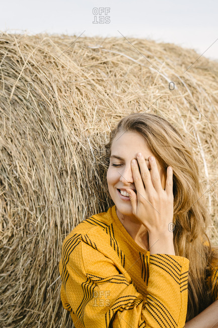 Happy woman sitting by bale of hay covering face
