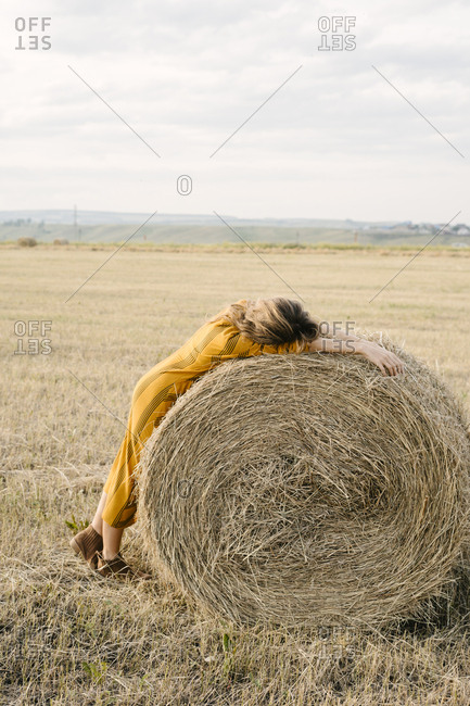 Blonde woman leaning on a bale of hay