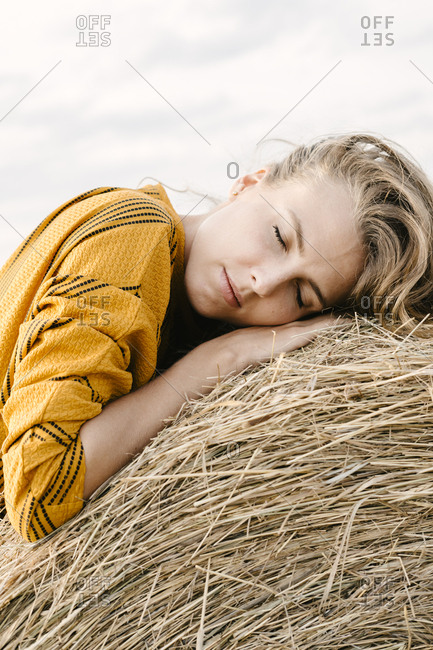 Blonde woman resting on a bale of hay