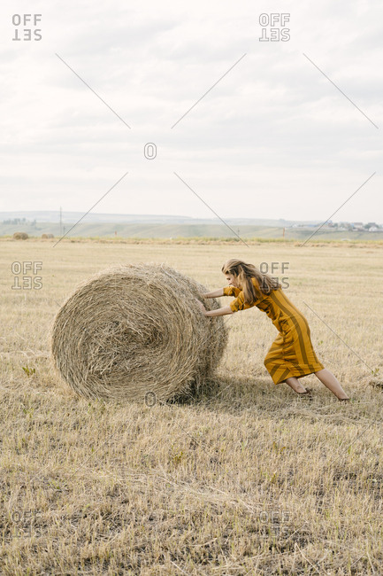 Blonde woman rolling a bale of hay